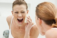 Woman scrubbing her face
