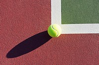 Tennis Ball Sitting on Edge of Tennis Court