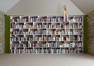 Girl sitting on top of bookshelves