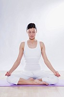 Mid adult woman with lotus position against white background
