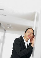 Young businesswoman listening to corridor door