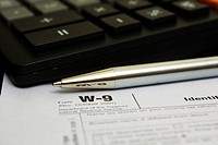 Pen and calculator on W_9 tax form