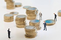 Stack of coins with business figurines on white background