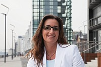 Germany, Cologne, Businesswoman with spectacles next to Rhine river and crane house in background, smiling, portrait