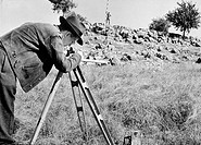 OIL SURVEYORS, c1944.A geologist (foreground) searches for an oil deposit in an American field with the help of his 'rod man.' Photographed c1944.