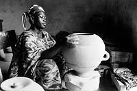 MALI: WOMAN POTTER, 1983.Woman making a clay pot at a ceramic factory in Bamako, Mali, 1983.