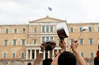 A protester holds a casserole in front of the Greek Parliament during a peaceful rally attended by thousands called through a social networking site- ...