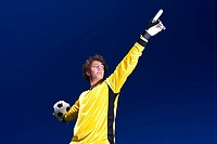 A goalkeeper ready to throw the ball to his team mates points to the direction