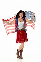 Young woman in cowgirl outfit waving american flag