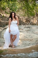 Trash the dress - young bride getting into a river