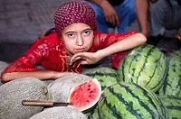An Uighur girl sitting by tasty melons and watermelons sold on the streets of Kashgar.