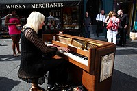 Scotland, City of Edinburgh, Edinburgh. A pianist performing on a pavement outside a Whisky Merchant on the Royal Mile during the Edinburgh festival f...