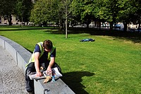 Scotland, City of Edinburgh, Edinburgh. A man taking a break from work reading a newspaper in St. Andrew Square
