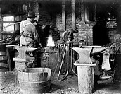 BLACKSMITH, c1906.An American blacksmith at work in his shop. Photograph, c1906.