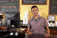 Malaysian business owner standing behind cafe counter