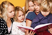Children reading a book, Sweden.