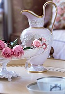 Ornate jug on table beside bowl with roses