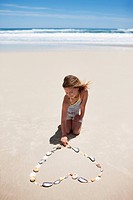 Girl making heart_shape with shells on beach