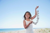 Girl holding shell necklace on beach