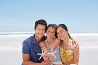 Family holding starfish on beach