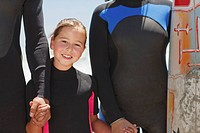 Family with surfboard holding hands in wetsuits