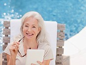 Senior woman with digital tablet sitting poolside (thumbnail)