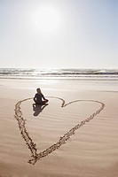 Woman sitting cross_legged in heart on beach