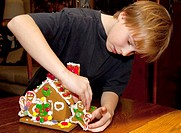 Boy age 10 concentrating on decorating Christmas gingerbread house  St Paul Minnesota USA