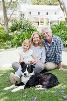 Grandparents with granddaughter and dog in park