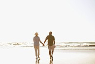 Senior couple holding hands and walking on beach