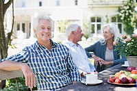 Senior friends sitting at table in garden