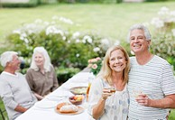 Couples drinking wine at table in garden