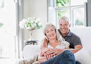 Senior couple hugging on sofa in living room