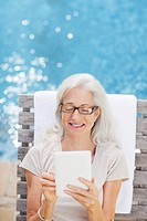 Senior woman using digital tablet poolside