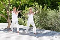 Couple doing yoga on patio