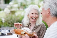 Senior couple eating bread