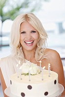 Portrait of woman holding birthday cake