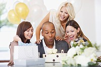 Friends watching man blow out candles on birthday cake