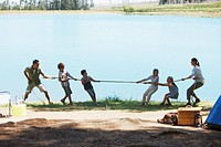 Family playing tug_of_war at campsite