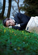 Mann wearing suit covered with newspaper sleeping in meadow