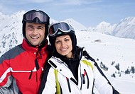 Couple in front of a mountain range, skiwear
