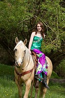A teenaged girl riding a horse