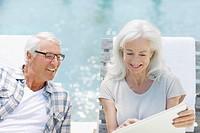 Senior couple using laptop at poolside