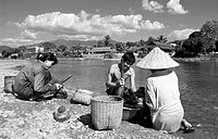 Three Laotians sit on Xong Nam and tap river algae