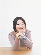 Young woman holding remote control, smiling, white background