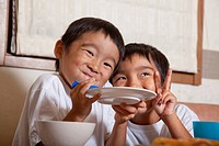 Boys holding a plate together and making a face, Japan