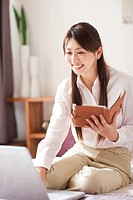 Young woman using laptop on bed, holding personal organizer