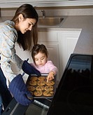 Caucasian mother and daughter taking cookies out of oven.