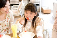 Little girl eating cake at a cafe with parents