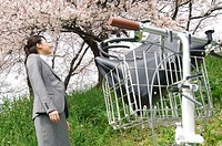Businesswoman looking up at cherry trees